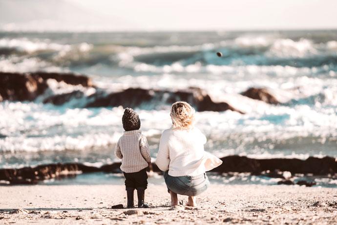 Mutter und Kind schauen am Strand in die Brandung - vielleicht kommt eine Flaschenpost mit den Wellen? Ein Foto von Taryn Elliott von Pexels